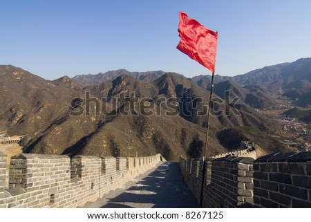 View of the Great Wall of China with red flag and blue sky