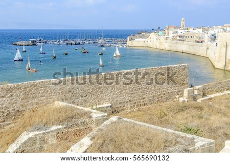 View of the harbor at the Old City of Akko, Israel. Sail boats and yachts at the old Acre sea port. Blue and calm waters of the Mediterranean Sea. Picturesque scenery of the ocean & small sailboats.