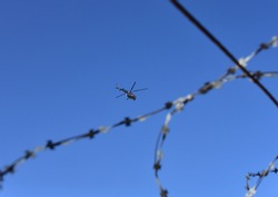 View of the helicopter in the air through the barbed wire against the blue sky