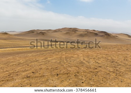 View of the highest sand dunes in the distance in the desert of the Paracas reserve in hot weather with haze in the air and cloudy skies