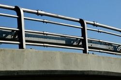 view of the highway overpass where the railing is formed by several railing pipes and barriers made of galvanic metal