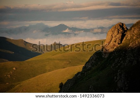 View of the hills covered with green grass in the foreground of high rocky hill in Bakhmaro, Adjara, Georgia