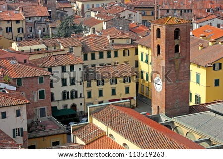 View of the historic part of Lucca in Italy, with an old clock tower and the narrow streets.