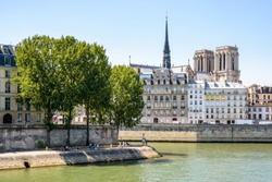 View of the Ile de la Cite on the river Seine in Paris, France, with Notre-Dame de Paris cathedral protruding above the buildings and the tip of Saint-Louis island in the foreground by a sunny day.