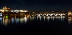 view of the illuminated Prague Castle and the Cathedral of St. Vitus and Charles Bridge on the Vltava River at night in the center of Prague in the Czech Republic, stars at sky
