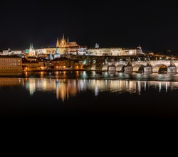 view of the illuminated Prague Castle and the Cathedral of St. Vitus and Charles Bridge on the Vltava River at night in the center of Prague in the Czech Republic