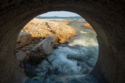 View of the interior of the sewer tunnel in an industrial factory released into the sea. Industrial waste water pollution Dirty sewage flows from the drains onto the sandy beach of the sea.
