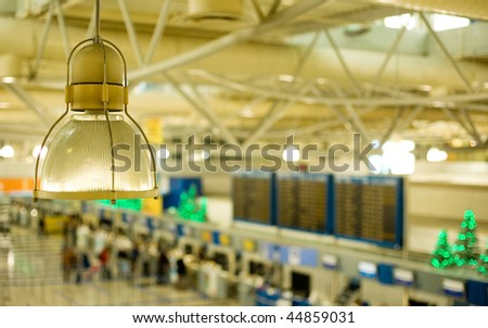 View of the international airport of Athens, Greece, with check-in counters, arrivals/departures board and decorated Christmas trees. Focus is on the lamp