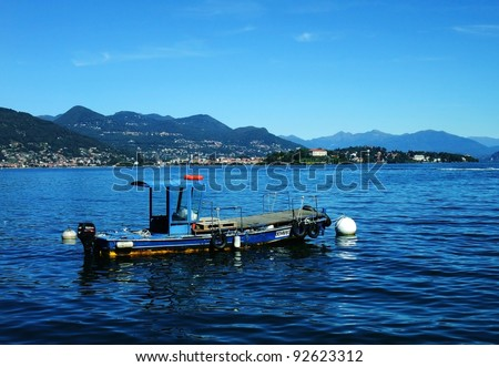 View of the Isola Madre and of the city of Verbania from the Isola dei Pescatori and of a local characteristic fishermen boat, Lake Maggiore, Piedmont, Italy