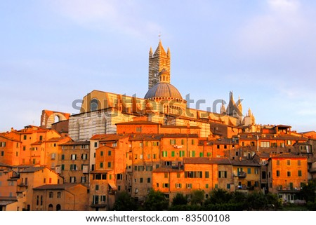 View of the Italian hill town of Siena under the glow of the setting sun