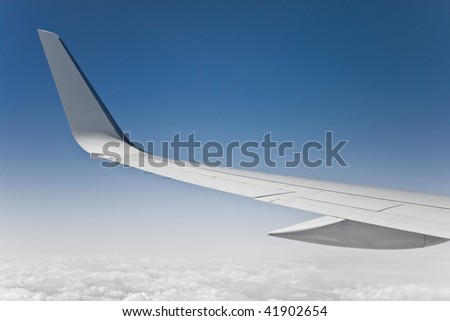 view of the jet plane wing and sky from passenger window