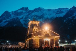 View of the Kedarnath temple lights at night with mountains in the background in Uttarakhand, India