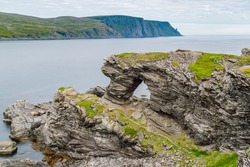 View of the Kirkeporten rock. This rock formation is a geological wonder; a fissure several metres wide in a cliff overhang shaped like a big gate, Skarsvag, Finnmark, Norway.