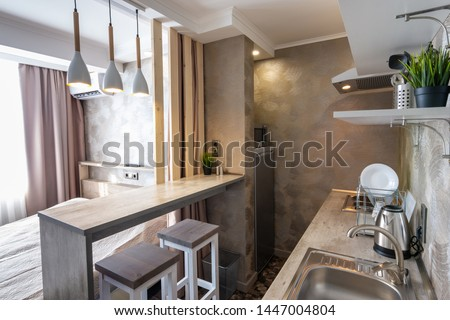 View of the kitchen and bar in a small hotel room - studio #1447004804