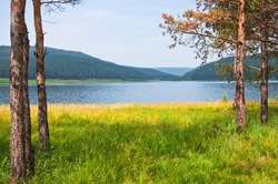 View of the lake and mountains. Beautiful summer landscape. Small depth of field