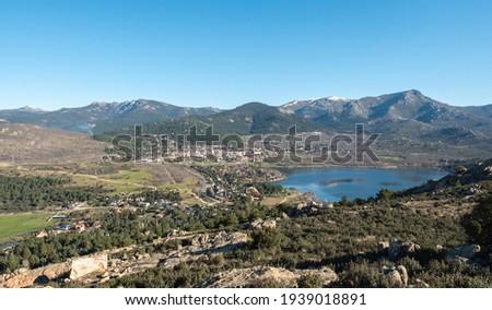 View of the lake and the village of Navacerrada Madrid with the Sierra de Guadarrama in the background - Siete Picos - Bola del Mundo - La Maliciosa Foto stock ©