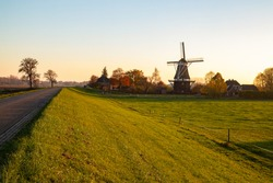 View of the landscape behind the dike with grazing sheep and a windmill in the countryside in the Netherlands.