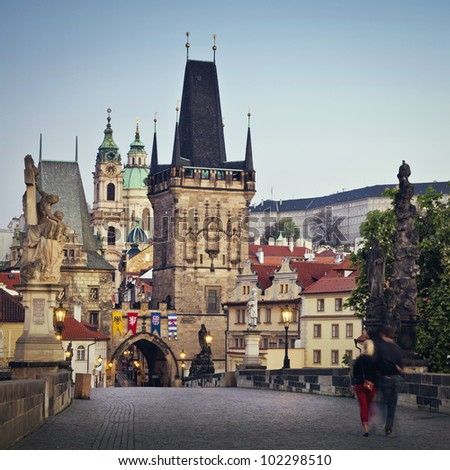 View of the Lesser Bridge Tower of Charles Bridge in Prague (Karluv Most) the Czech Republic. Couple walking in the morning.