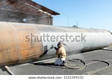 Photo of  View of the manuel sandblasting to the large pipe. Abrasive blasting more commonly known as sandblasting is the operation of forcibly propelling a stream of abrasive material against a surface.