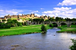 View of the medieval walled city of Carcassonne, France from a riverside park with historic bridge