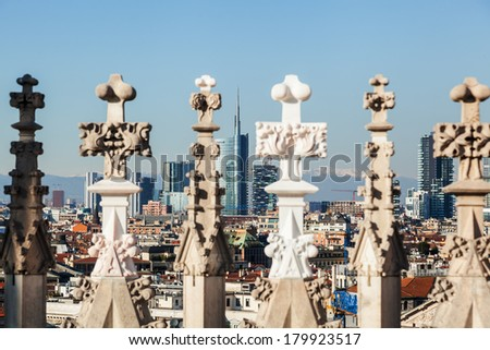 view of the Milan skyline through architectural details of the Milan Cathedral with focus on the background