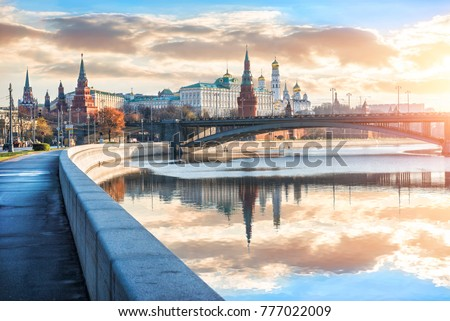View of the Moscow Kremlin with its towers and cathedrals and reflections in the Moscow River early sunny golden morning