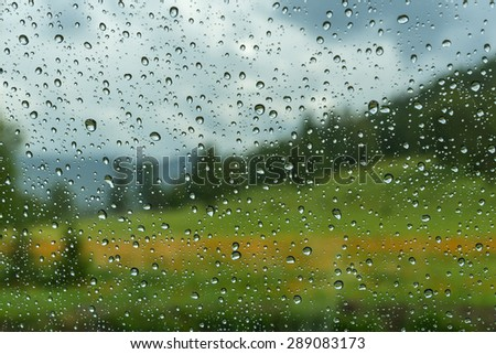 View of the mountain landscape with forest, meadow and flowers through the window glass of the car covered by rain drops