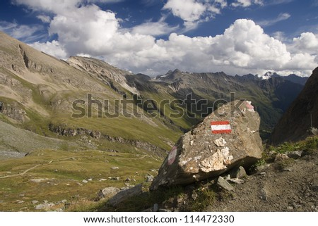 View of the mountains from the path with a mark of tourist trail on the rock. Hohe Tauern.