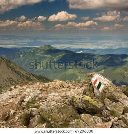 View of the mountains from the path with a mark of tourist trail on the rock. Rohace in Slovakian Western Tatra Mountains.