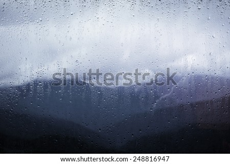view of the mountains through the glass with raindrops #248816947