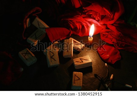 View of the mystical composition of wooden runes around the petals of red roses, a candle burns next to it and the burnt matches lie. Blur dark background #1380452915