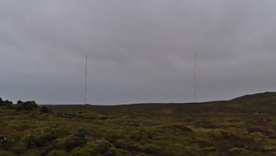 View of the Naval Radio Transmitter Facility (NRTF) of the US Navy with two towers located between moss covered lava fields near Grindavík, Reykjanes peninsula, Iceland on cloudy winter day.