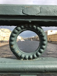 view of the Nevsky canal through a hole in the fence of the bridge you can see the houses along the canal and the gloomy sky