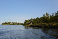 View of the Nikolsky skeet of the Valaam monastery from Lake Ladoga. Horizontal photo of a beautiful and calm nature, blue sky, clear water and green forest