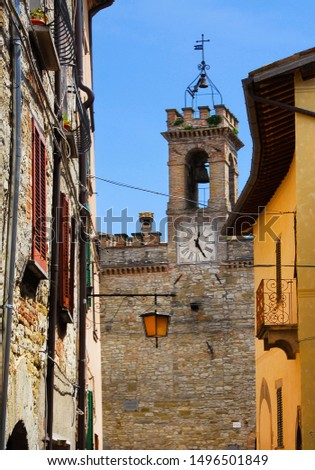 View of the old clocktower, erected in the 17th century, from a narrow lane in Pietralunga historic center, a small town in the Umbrian countryside