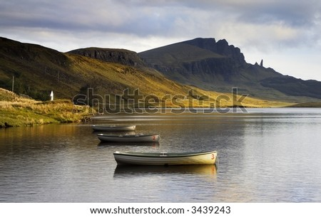 View of the Old Man of Storr over Loch Leathann in the Isle of Skye. Warm dawn sunlight lights the sides of the distant mountain which reflects in the calm, still waters of the Loch