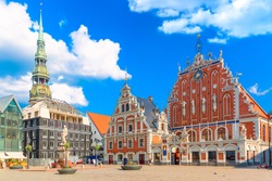 View of the Old Town Ratslaukums square, Roland Statue, The Blackheads House and St Peters Cathedral against blue sky in Riga, Latvia. Summer sunny day.