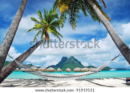 View of the Otemanu mountain , looking towards through the palms with hammock and the lagoon , Bora Bora , French Polynesia