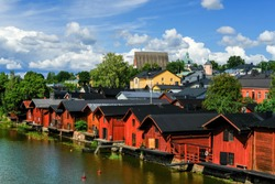 View of the picturesque river embankment in the old Finnish town of Porvoo with traditional red wooden warehouses.