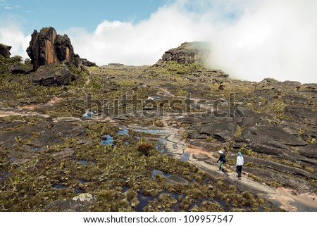 View of the plateau Roraima tepui and two trackkers - Venezuela, Latin America