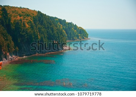 View of the precipitous shore of Cape Kadosh not far from Tuapse on an autumn fine day. Crystal clear sea water of greenish and blue colors. Pines grow over precipices. Abstract seascape. #1079719778