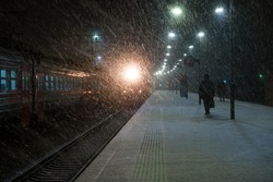 View of the railway platform in winter at night. You can see the soaking carriages, the bright light of the arriving train, and the silhouettes of people. It is snowing heavily. Scenery.