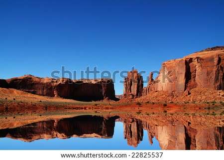 View of the red rock formations in Monument Valley with blue sky - stock photo