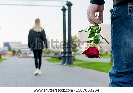 View of the red rose flower in the hand of the guy on the background of the girl leaving him in the city Park, square. Separation, resentment, quarrel, dislike, unloved