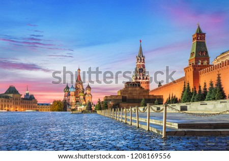 View of the Red Square in Moscow. St. Basil's Cathedral, Spasskaya Tower and the mausoleum in the early autumn morning and pink clouds in the sky #1208169556