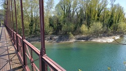 View of the Reno river from an iron bridge crossing the natural park on the hills around Bologna, Italy