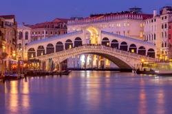 View of the Rialto Bridge and Grand Canal in a night lighthouse at sunset. Venice. Italy.
