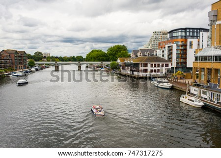 View of the river Thames with small boat passing and riverside apartments at Kingston-upon-Thames, a suburb of London, England, UK