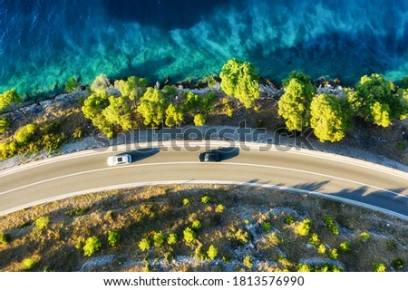View of the road along the coast from the drone. Travel by car in summer time. The sea coast and the road. The coast of Europe.