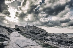 View of the road leading to the lighthouse on the island Frioul with a stormy sky. Marseille, South France. toning effect
